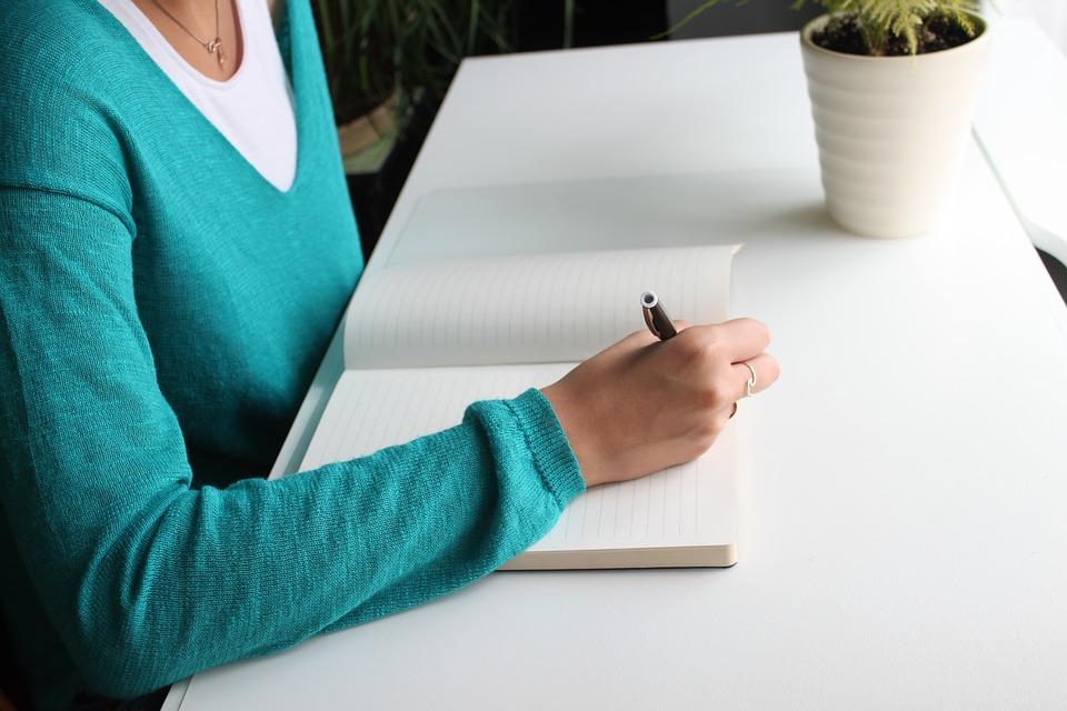 Mulher escrevendo em um caderno as suas decisões  sobre voluntariado.