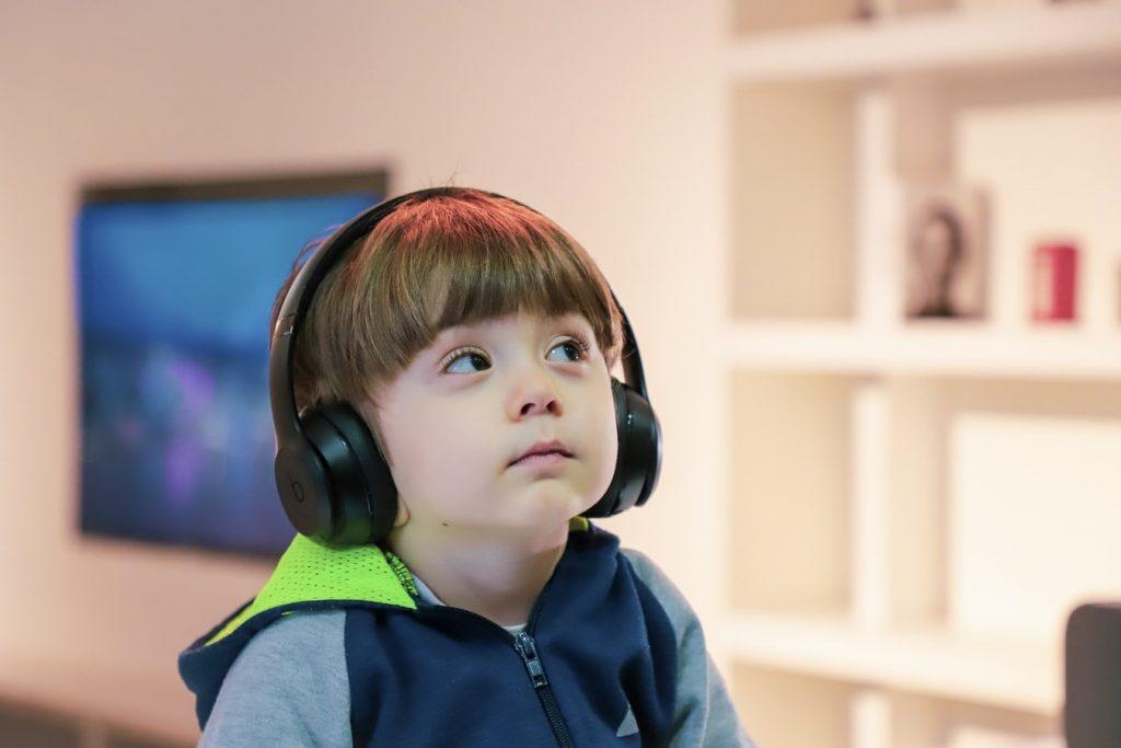 Uma criança se divertindo com um de seus passatempos, ouvir música.