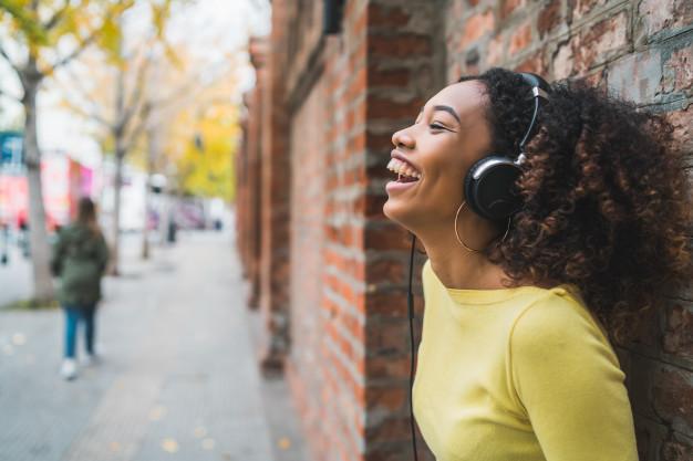 Mulher com fone de ouvido escutando música.