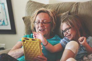 Avó e neta felizes jogando em um tablet