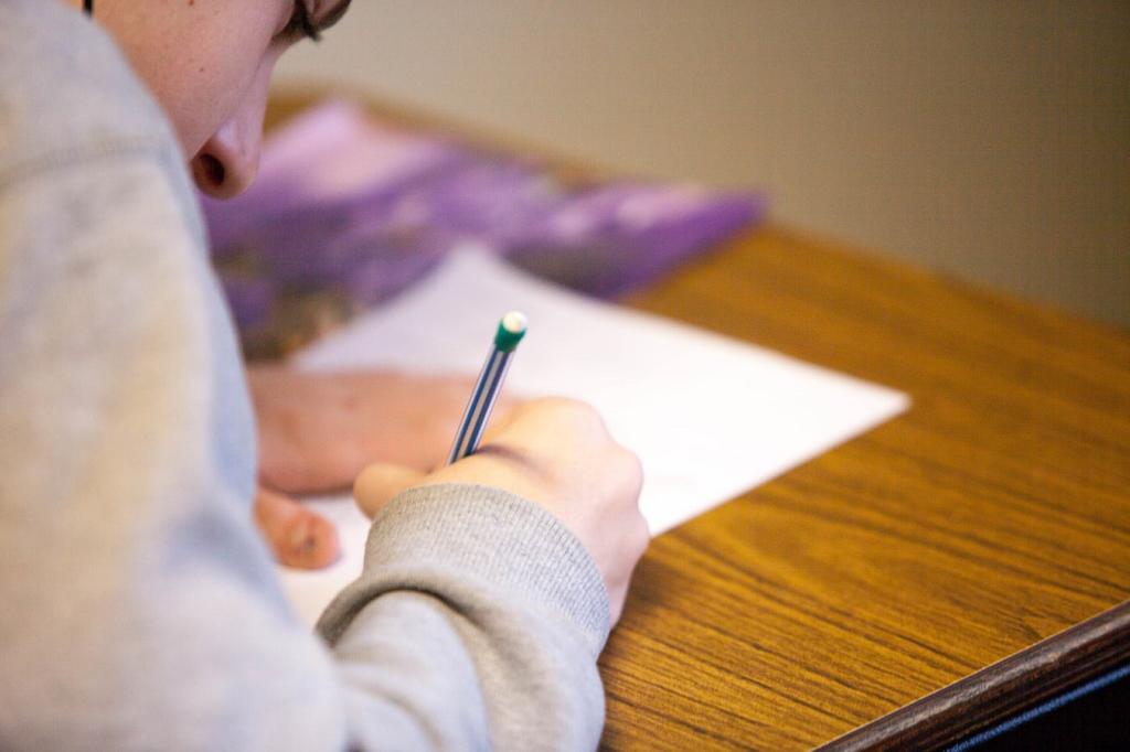Pessoa escrevendo em uma folha de papel