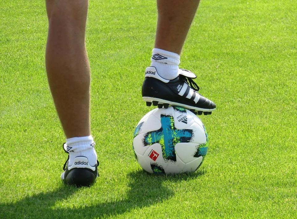 Jogador usando chuteira preta segurando a bola.