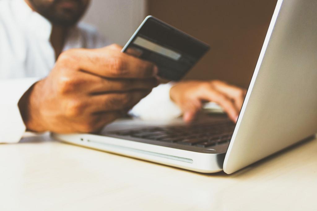 Homem mexendo no computador com o cartão de crédito na mão