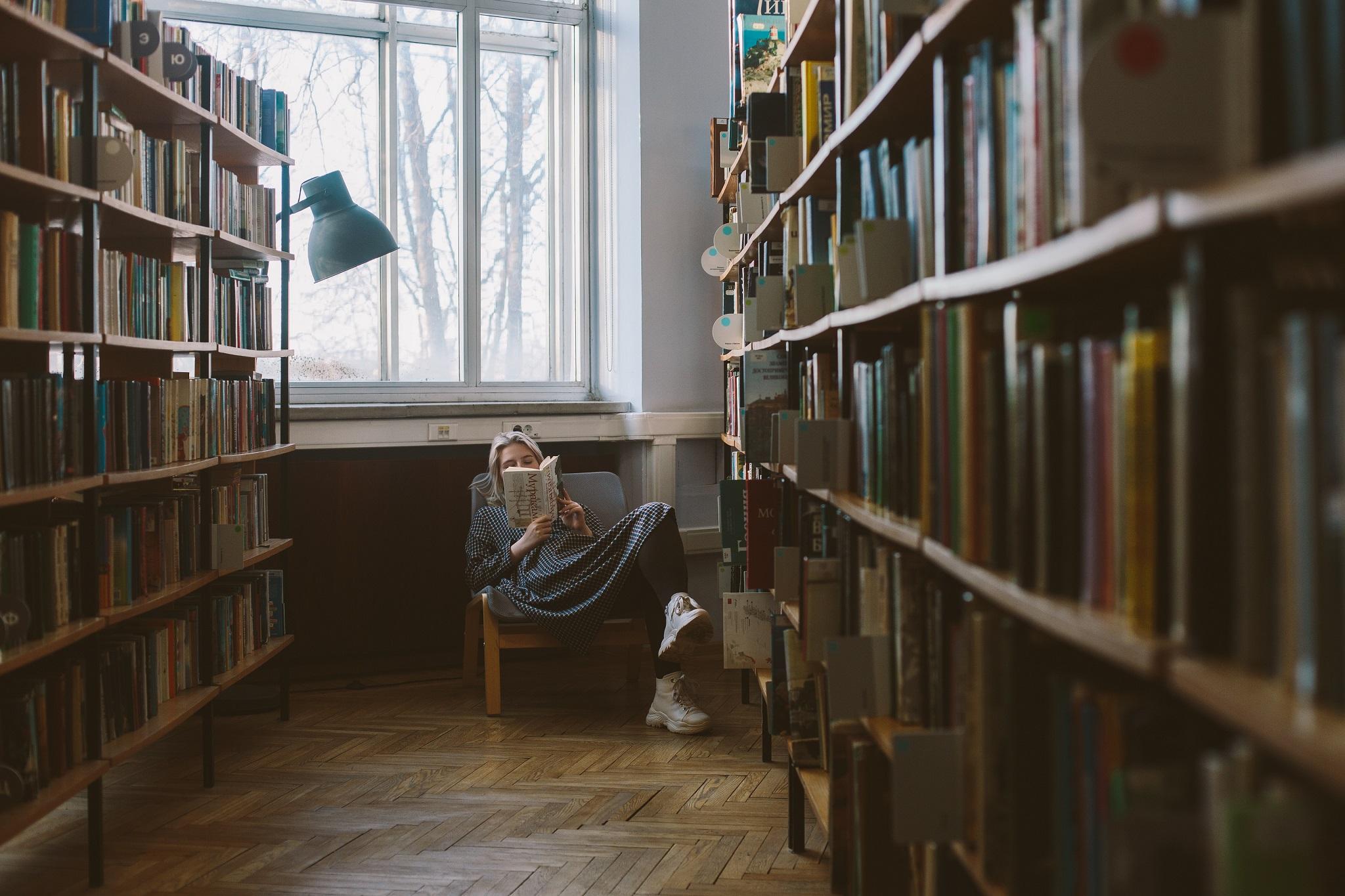 Mulher lendo em uma biblioteca com os melhores livros brasileiros.