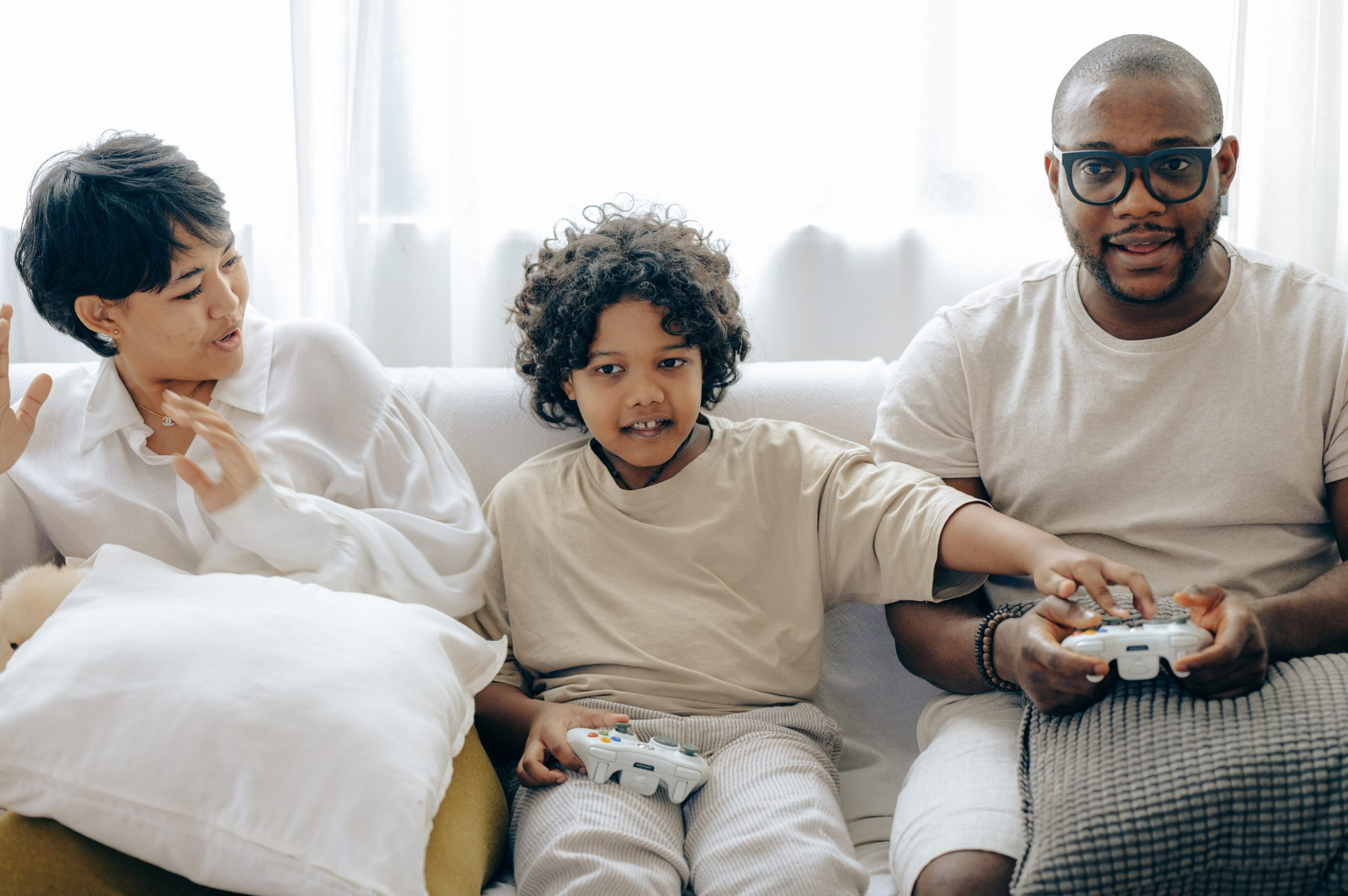 Pai, mãe e filho se divertindo enquanto jogam os melhores jogos para a família.