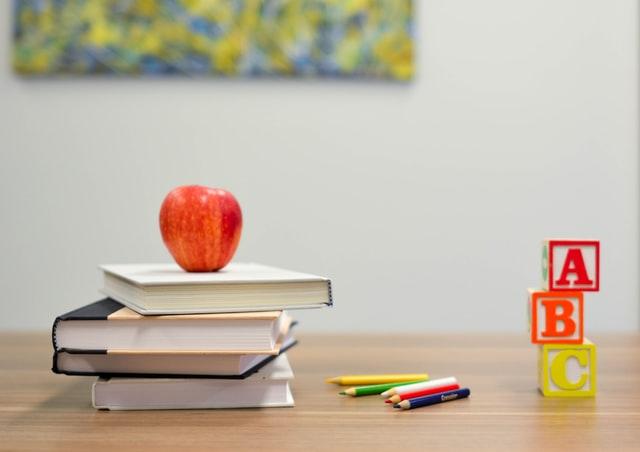 Imagem escolar, com uma mesa em que está uma pilha com 5 livros e em cima deles, uma maçã. Ao lado algumas canetinhas e a alça de uma caneta.