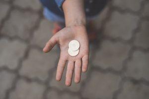 Em foco: mão de uma pessoa, aberta, com moedas.