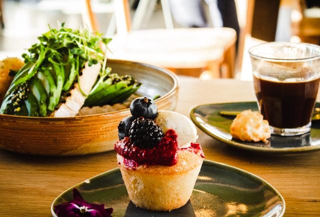 Cupcake com topo de frutas vermelhas em uma mea de refeição com um prato de salada de avocado e um prato com um copo de café e pães de queijo ao fundo.