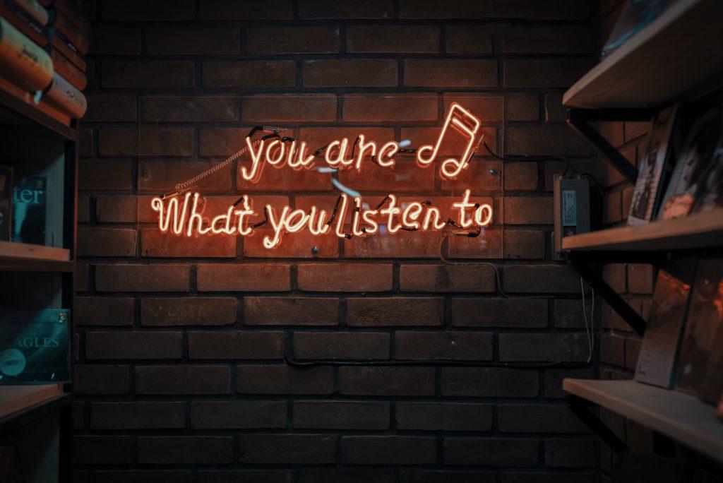 """Parede de tijolos escrito em inglês em neon: """"you are what you listen to"""". Tradução: """"Você também é o que você ouve"""""""