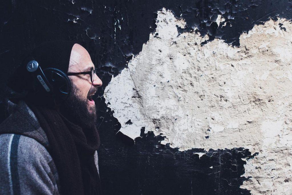 Homem cantando em frente a uma parede com cores em preto e branco, onde a cor branca ecoa de sua boa como se fosse o som da sua voz