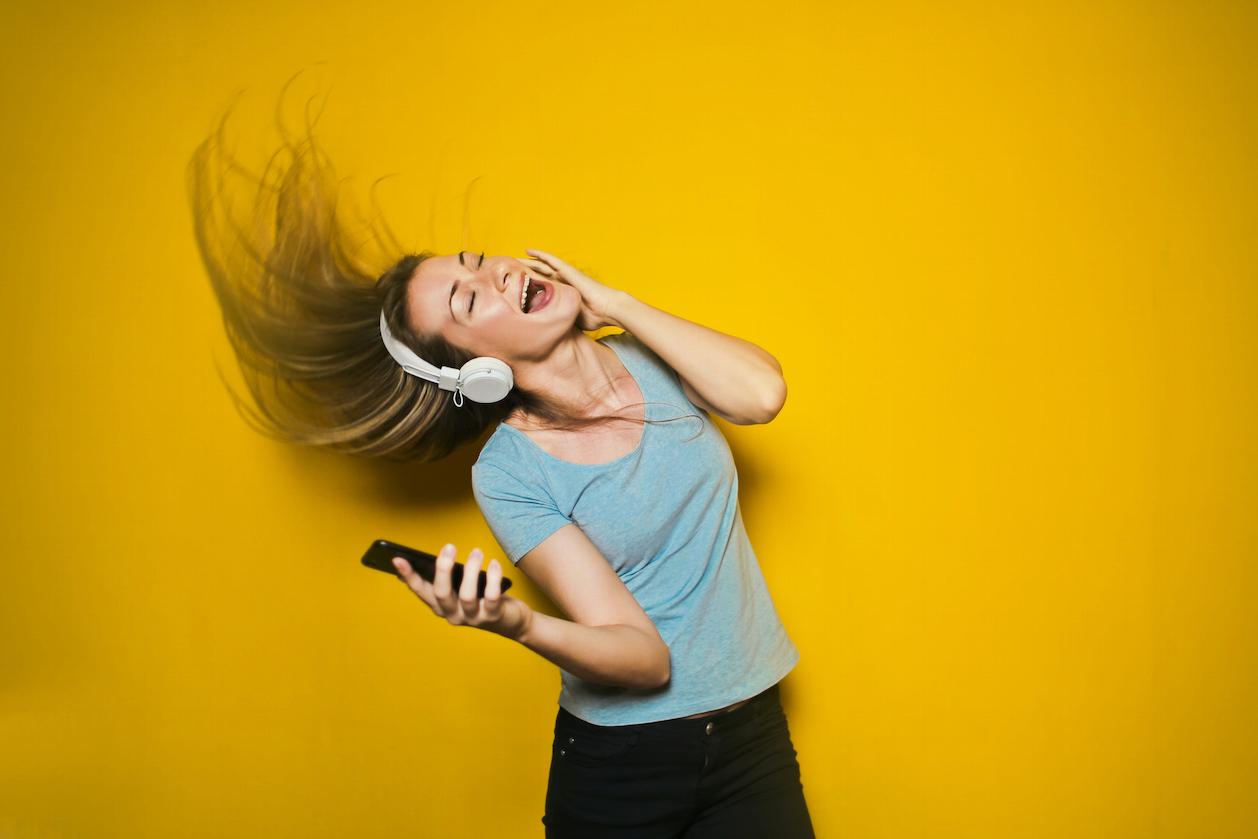 Mulher ouvindo música e cantando para aprender inglês ouvindo músicas