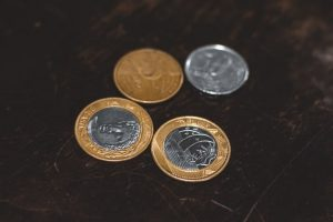 moedas de 1 real e cinquenta centavos sobre uma superfície de mármore escuro