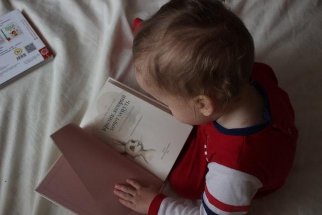 bebê sentado na cama lendo livro