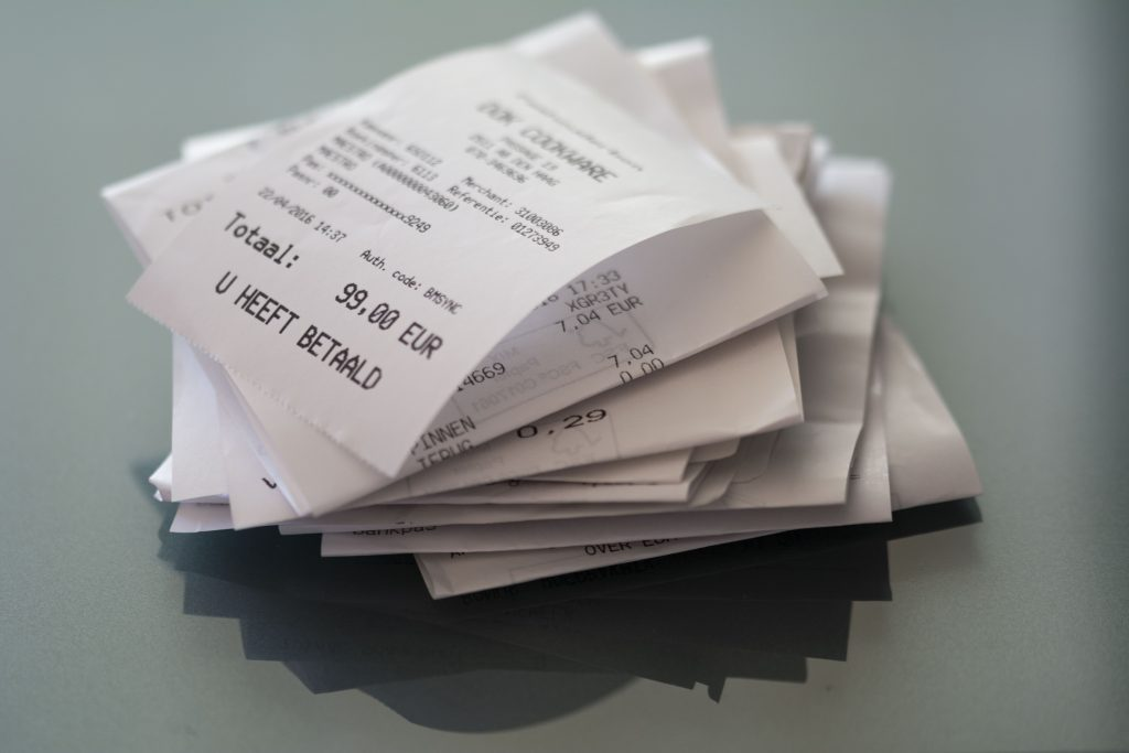 Notas de pagamento em cartão sobre uma superfície cinza opaca.