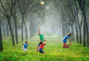 Crianças brincando em uma clareira verde