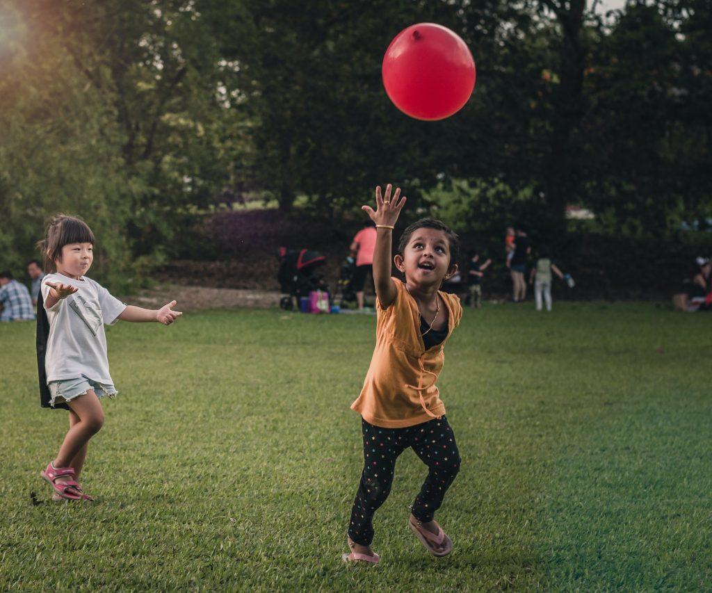 Crianças brincando com uma bola vermelha.