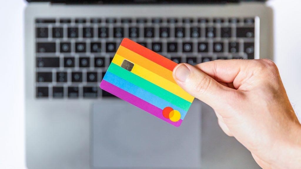 Mão segurando cartão de crédito com estampa de arco-iris, sobre teclado de notebook.