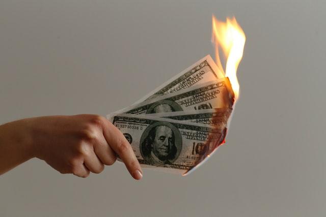 Mão segurando notas de dólar que estão pegando fogo.