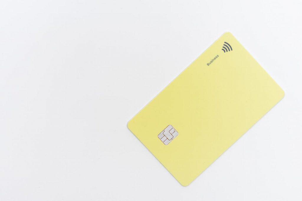 cartão de crédito amarelo, na diagonal, sobre fundo branco.