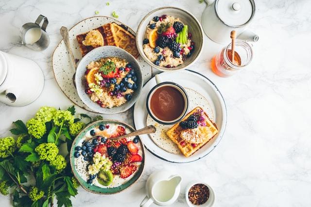 mesa branca de marmore com vários pratos brancos que compõem um café da manhã com diversos pratos gostosos como waffles, saladas de frutas vermelhas, mel, cobertura de chocolate e etc.