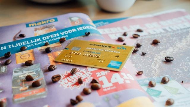 Crartão de crédito dourado sobre catálogo de viagens.