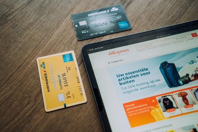 Lateral de um tablet aparece ao lado de dois cartões de crédito, um dourado na lateral vertical e um preto na lateral horizontal superior. Na tela do tablet aparece um portal de compras online.