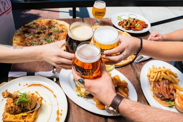 Três mãos em foco, brindando com cervejas artesanais, sobre mesa com vários pratos.