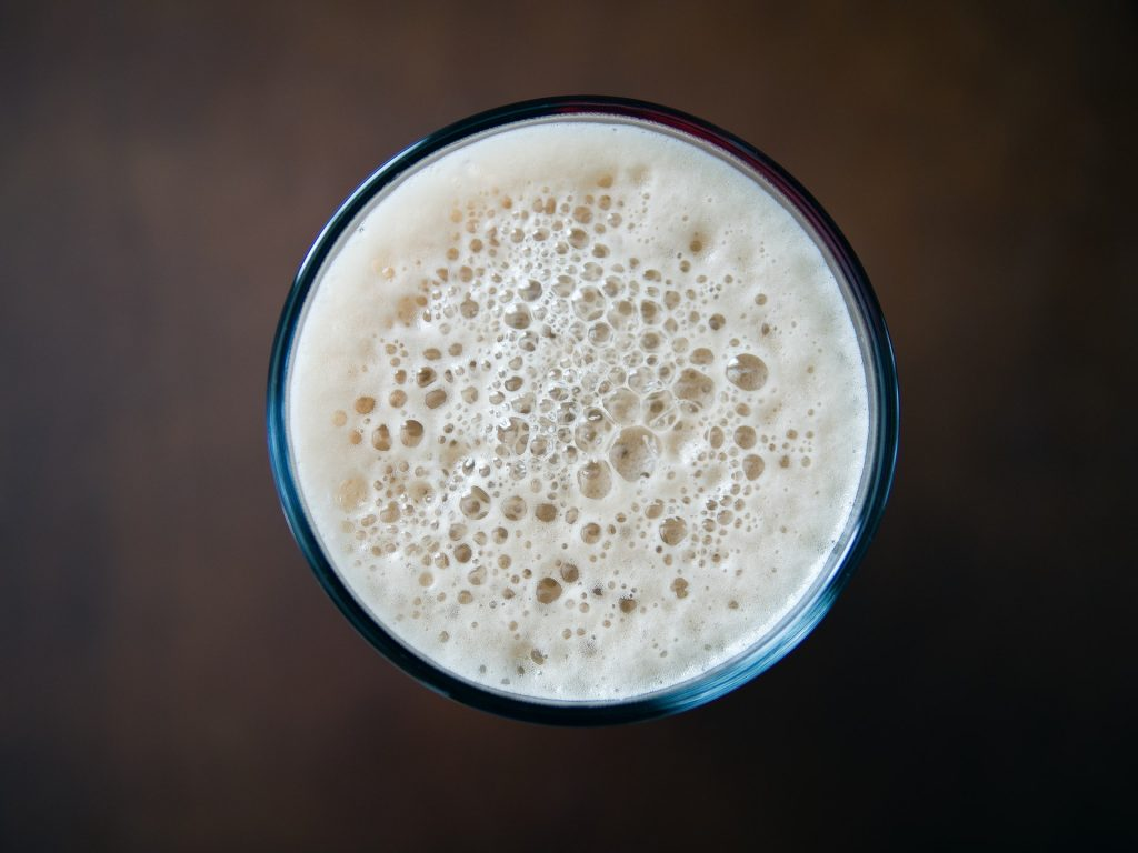 copo de cerveja focado de cima mostrado apenas a espuma da mesma.