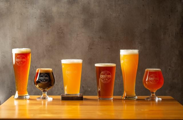 vários copos espececíficos para apreciar cada tipo de cerveja, cheios de cervejas, sobre uma mesa de madeira envernizada. Ao fundo uma parede de cimento queimado.