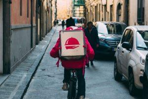 Entregador estilo ifood indo de bicicleta por uma rua