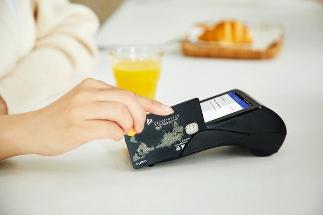 pessoa usando máquina de cartão de crédito.