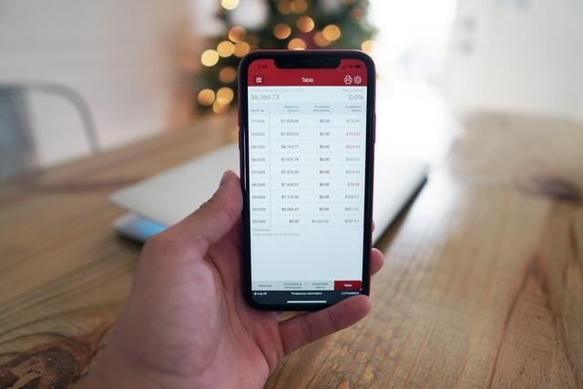 Celular na mão, com a tela apresentando números.