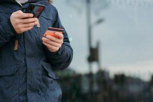Pessoa de jaqueta chumbo realizando transação por celular