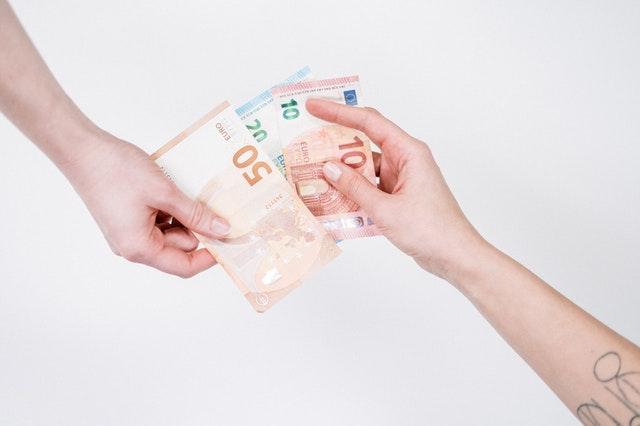 duas mãos trocando dinheiro