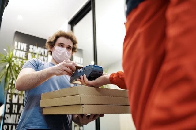 Homem entregando pizza de máscara de proteção.