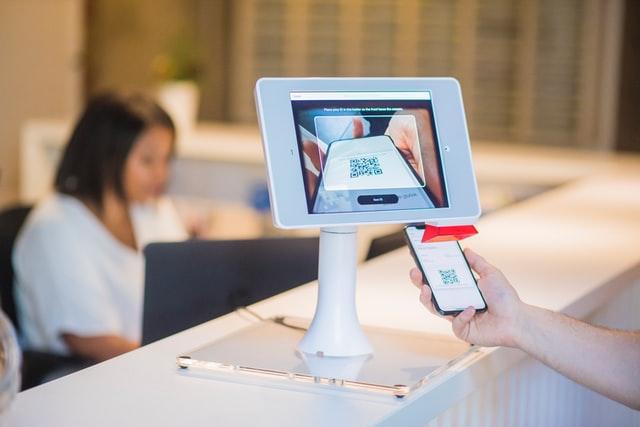 Computado moderno, branco, escaneando do QR Code de um celular. Ao fundo atendente, distante, trabalhando.