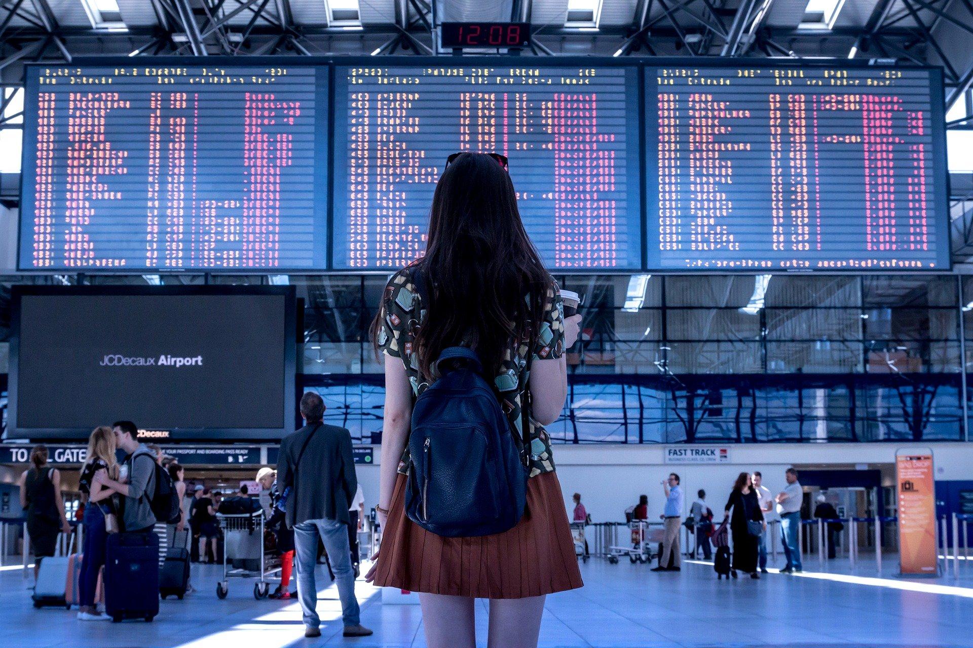Na imagem há uma mulher em um saguão de aeroporto, vendo o painel dos embarques e desembarques.