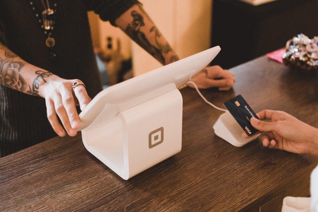 Na imagem há uma pessoa finalizando a compra com o cartão de crédito e uma outra pessoa no caixa do empreendimento comercial.