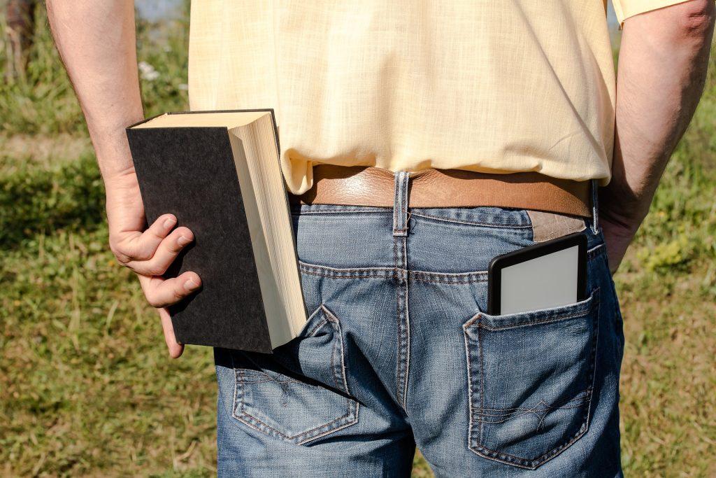 Ao centro da imagem há um homem de costas com um e-reader em seu bolso direito e está tentando colocar um livro em seu bolso esquerdo.