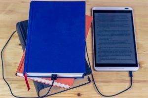 Do lado esquerdo da imagem há uma pilha de 3 livros conectados a um e-reader.
