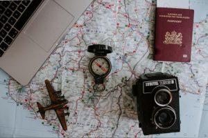 Ao fundo um mapa, apoiado em uma superfície plana. Em cima do mapa, estão apoiados uma câmera, um passaporte, uma bússola, um avião de brinquedo e ao canto superior esquerdo, parte de um notebook