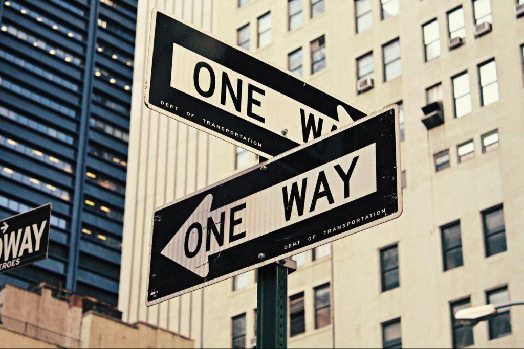 Placas na rua sinalizando caminhos opostos. Ao fundo, prédios da cidade.