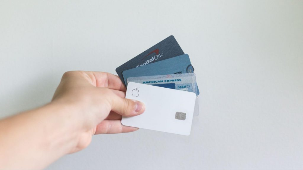 Mão humana segurando quatro cartões de crédito ao centro, com um fundo branco.