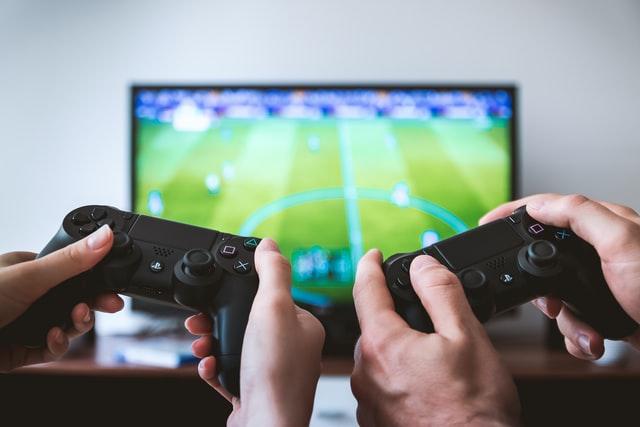 Duas mãos segurando dois controles de vídeo game lado a lado, em frente a uma televisão, onde um jogo de futebol aparece.