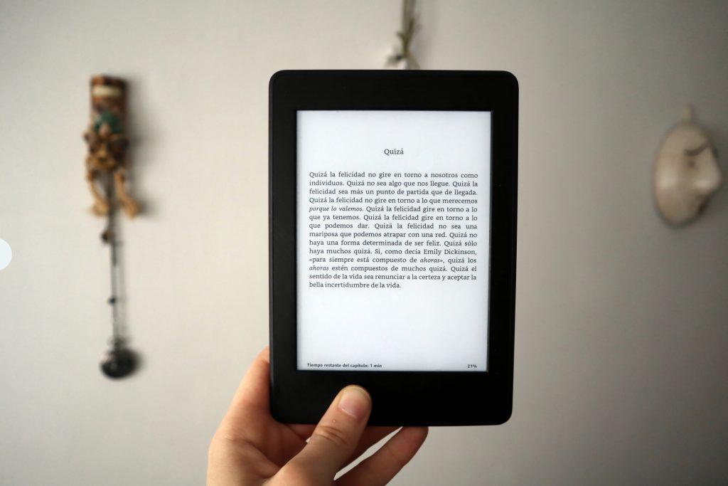 Ao centro da imagem há um indivíduo segurando um e-reader.