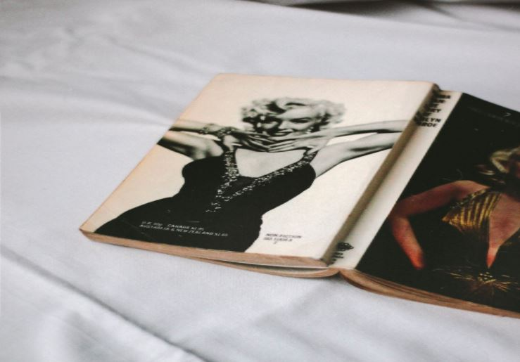 Revista de moda aberta e virada com a capa para cima sobre uma cama. Na capa a atriz Marilyn Monroe.