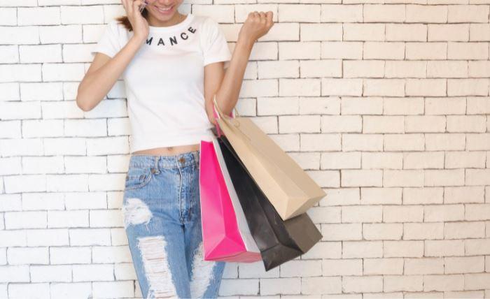 Mulher segurando sacolas de compras enquanto fala ao celular.