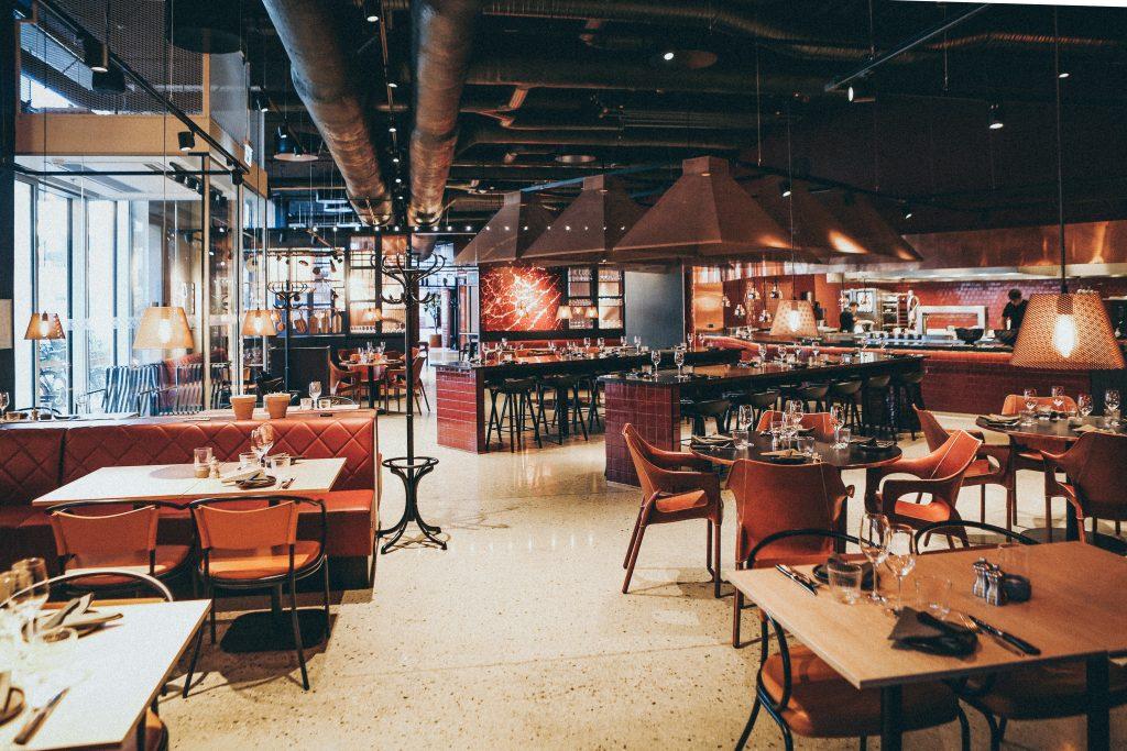 Na imagem há um salão de um restaurante com poucas pessoas, com diversas mesas e cadeiras disponíveis.
