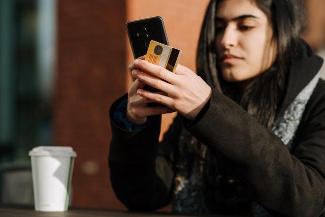 Mulher vista da lateral mexendo em seu celular enquanto segura seu cartão.