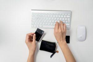 pessoa digitando num teclado com a mão direita e num segurando um cartão preto na outra mão.